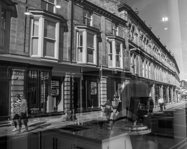Reflections in a shop window show the buildings on the opposite side of the street.