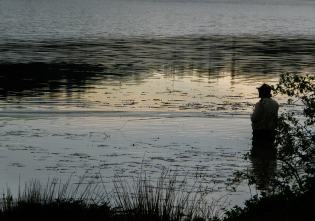 A fisherman stands waist deep in a resevoir in the late afternoon.