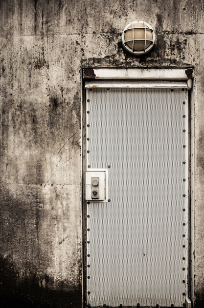 A heavily protected door in a concrete wall.