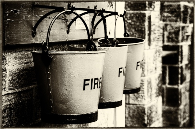 Three fire buckets on hooks.
