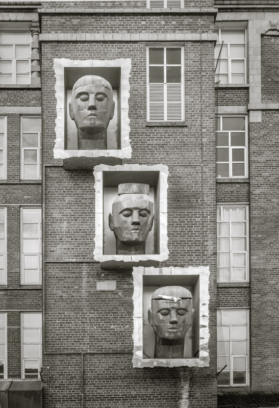 A sculpture of three heads on a mill wall